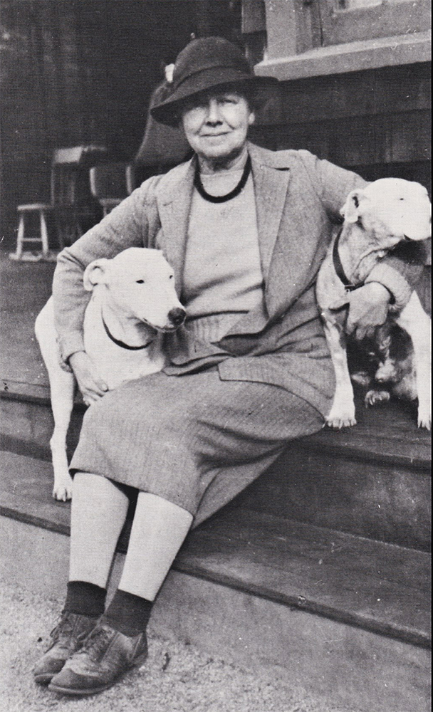 Photograph of Gertrude Fiske seated on porch steps with dogs