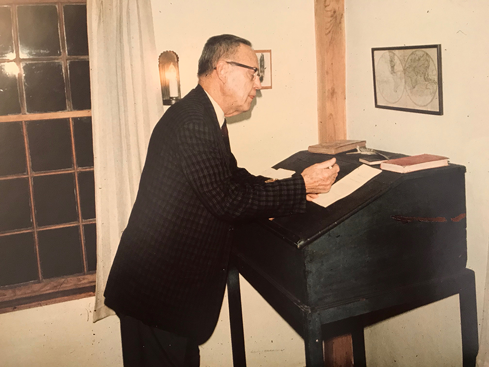 Harold Travis standing at Isaac Fiske's writing desk