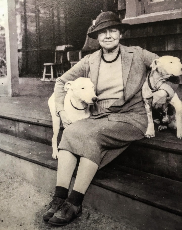 Photo of Gertrude Fiske sitting on porch with dogs